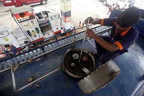 An employee measures diesel in a tanker before unloading at a fuel station in Kolkata.