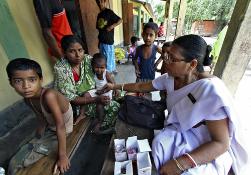 A health official attends to the villagers from Muslim communities affected by ethnic riots inside a relief camp near Bilasipara town in Assam.