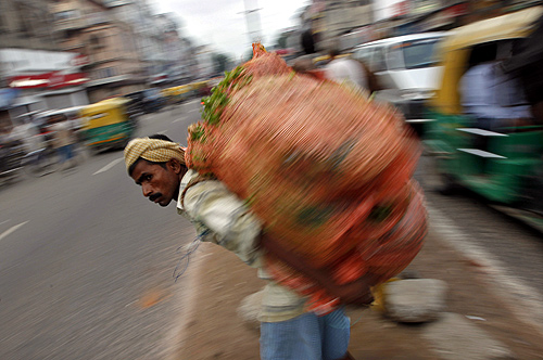 A labourer carrying a sack of vegetables waits to cross a road in the old quarters of Delhi.