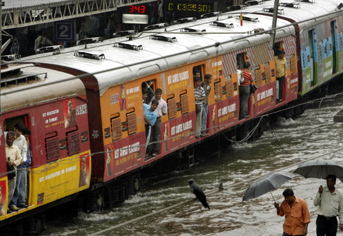 A train moves through a flooded track after heavy rains in India's financial capital Mumbai.