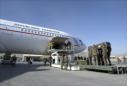 French troops load the flag-draped coffins of four soldiers onto a French plane during a ceremony at the