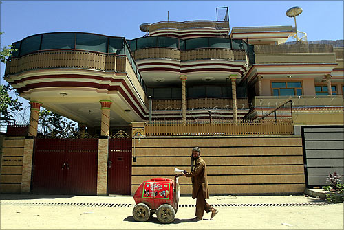 An Afghan man sells ice cream as he walks in front of a Swiss-based Medair office in Kabul.