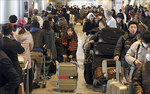 Passengers queue to check into a flight at Narita airport, east of Tokyo.