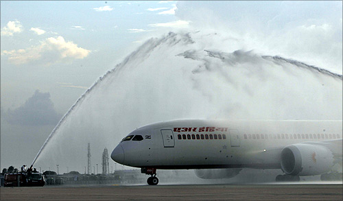 Air India's Dreamliner Boeing 787 is given a traditional water cannon salute by the fire tenders upon its arrival at the airport in New Delhi.