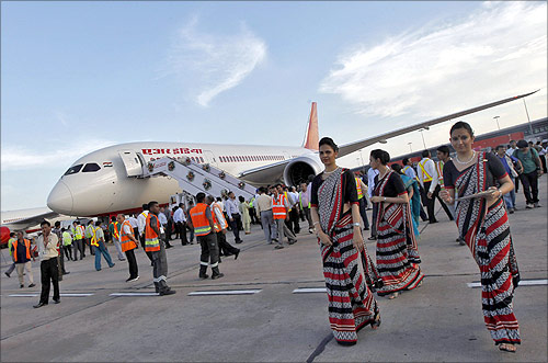 Air hostesses walk next to the parked Air India's Boeing 787-800 Dreamliner upon its arrival at the airport in New Delhi.