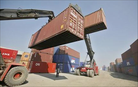 Workers prepare to stack containers at Thar Dry Port in Sanand in Gujarat.