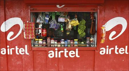 A vendor waits for customers at his grocery shop, painted with an advertisement for Bharti Airtel in Kochi.