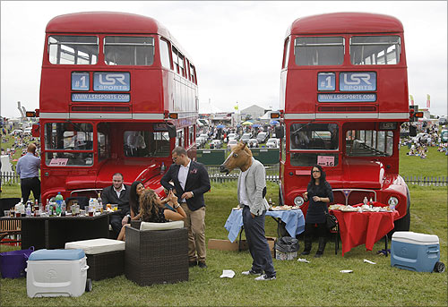 Spectators picnic between a pair of double decker buses during Ladies Day at the Epsom Derby festival in Epsom, southwest of London.