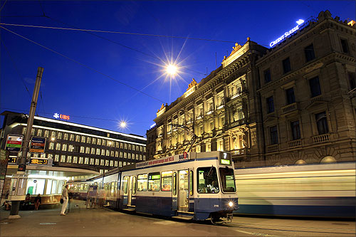 Trams drive past the offices of Swiss banks UBS (L) and Credit Suisse at Paradeplatz square in Zurich.
