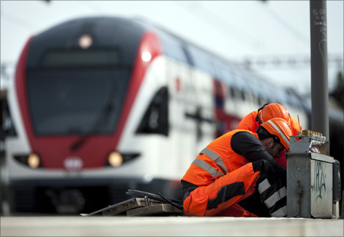Employees of the Swiss Federal Railways (SBB) perform maintenance operations in front of the new regional two-floor train connecting Geneva and Lausanne.