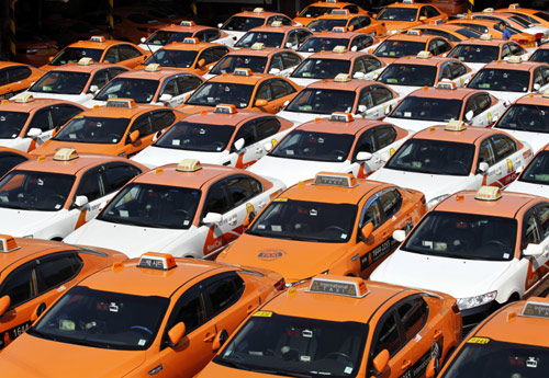 An engineer (top R) checks taxis parked at the compound of a taxi company, after drivers halted their operations to attend a nationwide strike in Seoul.