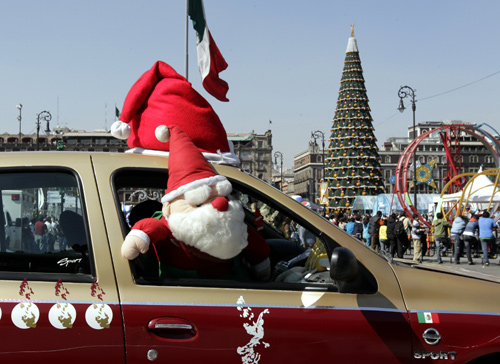 A Santa Claus plush toy is seen on the window of a taxi it drives past Zocalo Square in Mexico City.