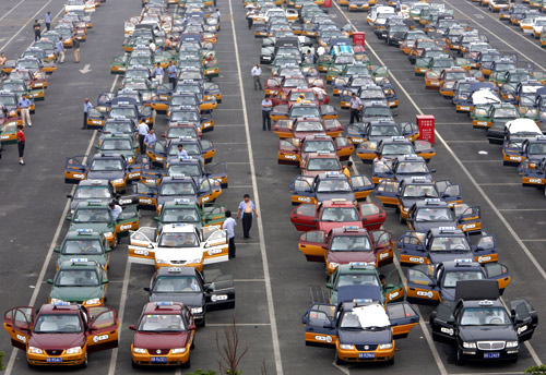 Taxi drivers queue at a parking lot while waiting for passengers at the new Beijing Capital International Airport.