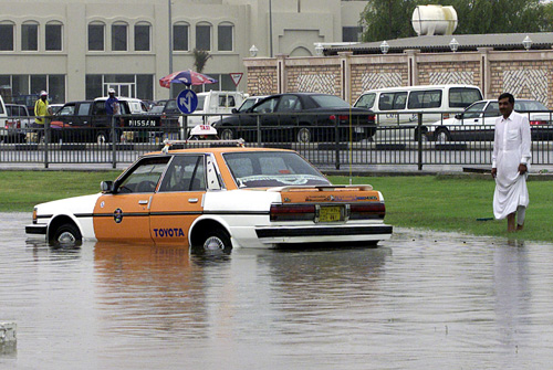A taxi driver looks in dismay at his car after it got stuck on a flooded road in Doha.