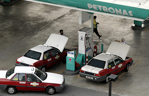 Taxis pump natural gas at a Petronas station in Kuala Lumpur.