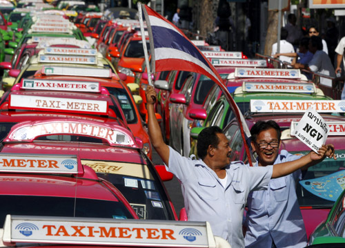 Taxi drivers wave a Thai flag during a rally in front of the Government House in Bangkok.