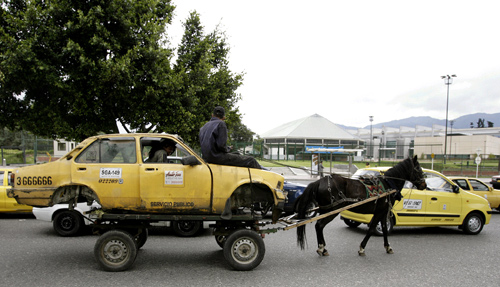 The remains of a taxi are transported by two men on a horse drawn cart on a main street of Bogota, Colombia.