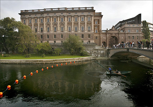 A fisherman lifts his net from a canal next to Sweden's Riksdagshuset, or Parliament Building in Stockholm .