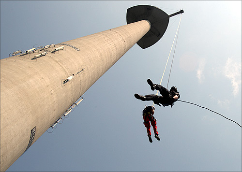 A police officer and a paramedic rope down the 252 metres (827 feet) high Donauturm tower, Austria's tallest building, during a joint exercise in Vienna.