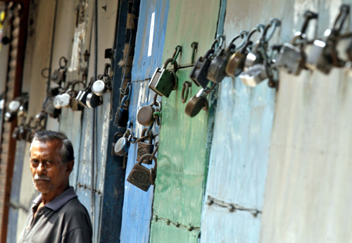 A man stands in front of closed shops during a nationwide strike in Kolkata.