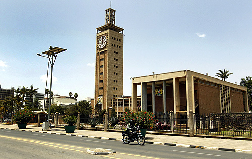 A motorcyclist rides past the Kenyan Parliament House clock tower in the capital Nairobi.