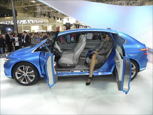 A model poses inside a Denza electric car at the 2012 Beijing International Automotive Exhibition in Beijing.