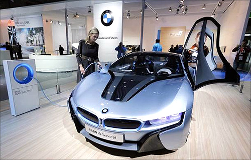 A model poses next to a BMW electric i8 Concept car during a press preview day at the AMI Auto Show in Leipzig.
