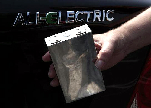 A woman displays a 333 volt single-cell battery in front of a Coda sedan at the sixth annual Alternative Transportation Expo and Conference (AltCar) in Santa Monica, California.