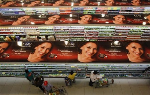 People shop down the aisles of a supermarket in Mumbai.