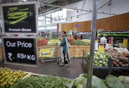 A woman pushes a shopping trolley in the fresh food section at a retail supermarket in Mumbai.