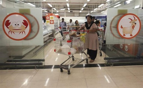 A woman pushes a trolley as she exits the meats section of a Reliance Fresh supermarket in Mumbai.