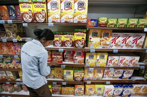 An employee arranges breakfast cereals on the shelves of a supermarket in Mumbai.
