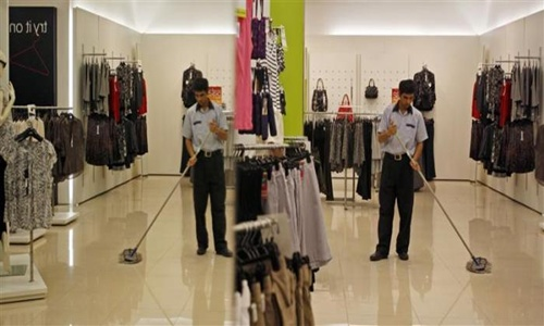 A worker is reflected in a mirror as he sweeps the floor at one of the retail outlets of Marks and Spencer in Mumbai.