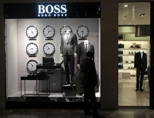 A man looks at a shop window outside the Hugo Boss showroom inside a shopping mall in Mumbai.