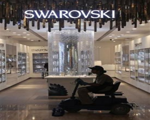 An employee operates a floor cleaning machine in front of a Swarovski showroom inside a shopping mall in Mumbai.