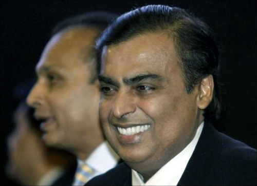 Mukesh Ambani (R), chairman of Reliance Industries, smiles as his brother Anil Ambani, chairman of Reliance Group, stands behind him during the inauguration ceremony of the Vibrant Gujarat global investor summit at Gandhinagar in Gujarat January 11, 2013.