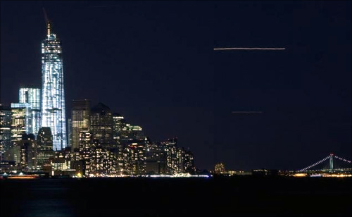 The lights of an airplane landing at La Guardia airport streak across the sky past the new World Trade Center (left) in New York.