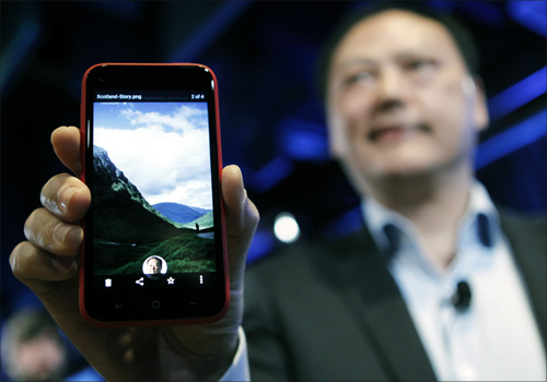 HTC CEO Peter Chou holds an HTC First phone showing the new app Facebook Home for Android during a press event in Menlo Park, California.