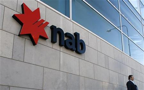 An office worker waits next to a branch of National Australia Bank (NAB) in east Sydney.
