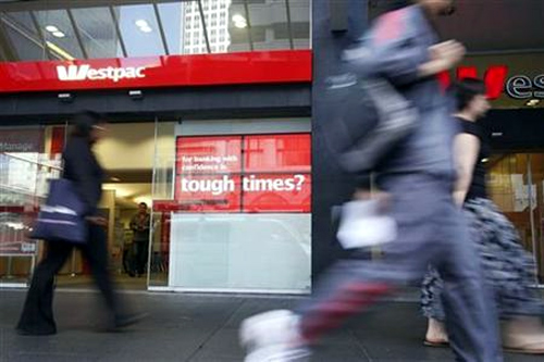 Pedestrians walk past an electronic display board in front of a Westpac bank in Queen Street, downtown Auckland.