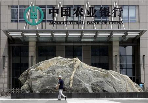 A pedestrian walks past a logo of Agricultural Bank of China in front of its headquarters in Beijing.