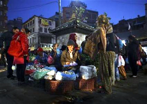A street vendor sells mushrooms to a customer at Ashon, one of the busiest market places, in central Kathmandu.