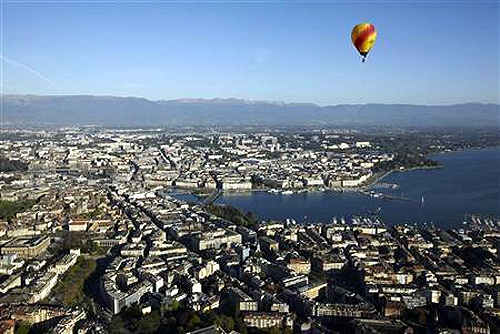 A hot air balloon flies above the city of Geneva.