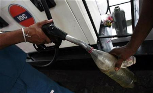 A worker fills up a bottle at a Lanka India Oil fuel station in Colombo.