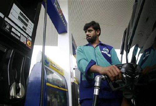 A service station attendant fills a car with fuel at a petrol station in Islamabad.