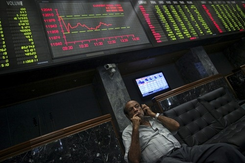 An investor talks on his mobile phone while sitting near an electronic board displaying stock prices at the Karachi Stock Exchange.