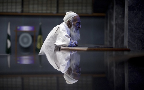 An elderly man is reflected on a marble table as he monitors share prices on a screen during a trading session at the Karachi Stock Exchange.