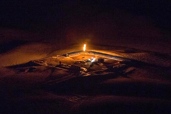 An aerial image shows a natural gas flare after sunset outside of Williston, North Dakota.