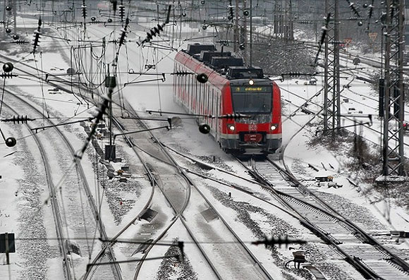 A regional train travels along snow-covered rails near Essen in Germany.
