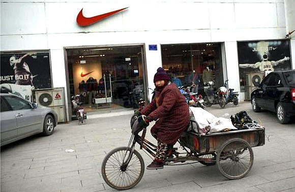 A woman rides past a clothing store at the business area of Jiaozuo, China's central Henan province.